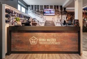 George Walstock Maastricht - Luxe balie met witte freesletters en dibond fotowand